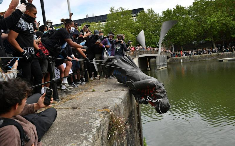 Protesters throw the statue of Edward Colston into Bristol harbour during a Black Lives Matter protest rally, in memory of George Floyd. Colston was a merchant who was involved in the Atlantic slave trade - Ben Birchall/PA