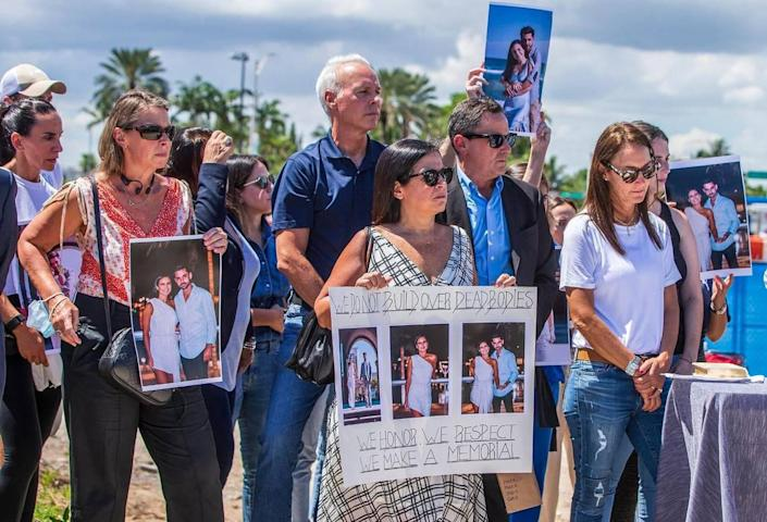Surfside Mayor Charles Burkett, center, joined families of Surfside collapse victims as they held a press conference Thursday, Sept. 23, 2021, at the site of the Champlain Towers South Condo collapse to call for a memorial to be constructed where 98 victims died in Surfside, Florida.