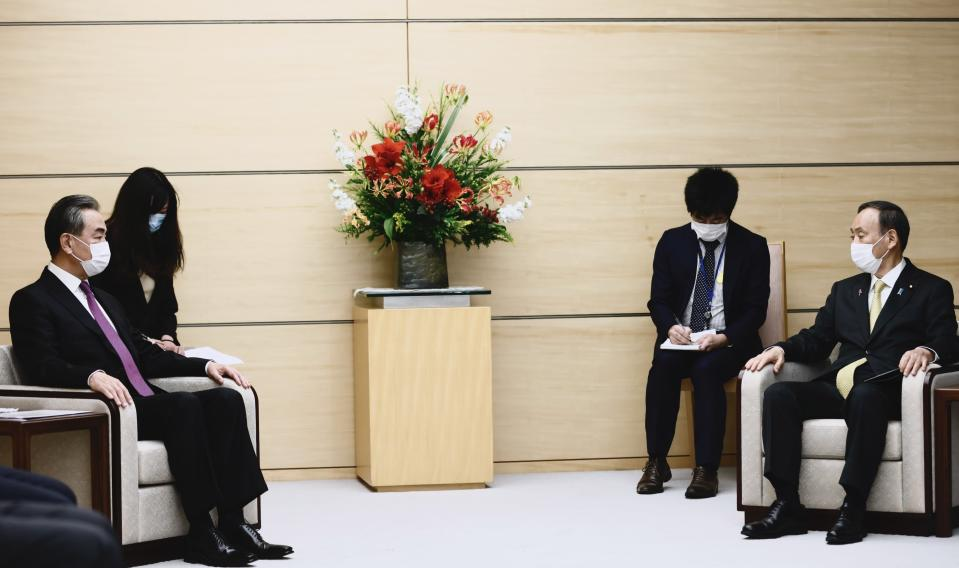 Japan's Prime Minister Yoshihide Suga, right, sits with China's Foreign Minister Wang Yi, left, at the start of their meeting in Tokyo, Wednesday, Nov. 25, 2020. (Behrouz Mehri/Pool Photo via AP)