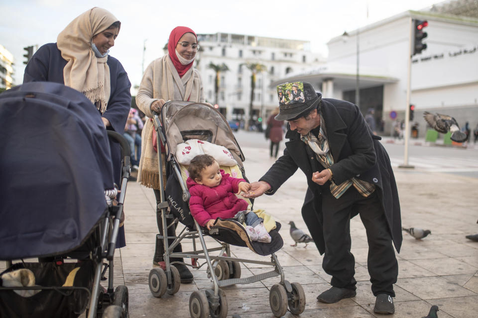 Belhussein Abdelsalam, a Charlie Chaplin impersonator reacts while performing for some children, in an avenue in Rabat, Morocco, Thursday, Dec. 17, 2020. When 58-year-old Moroccan Belhussein Abdelsalam was arrested and lost his job three decades ago, he saw Charlie Chaplin on television and in that moment decided upon a new career: impersonating the British actor and silent movie maker remembered for his Little Tramp character. (AP Photo/Mosa'ab Elshamy)