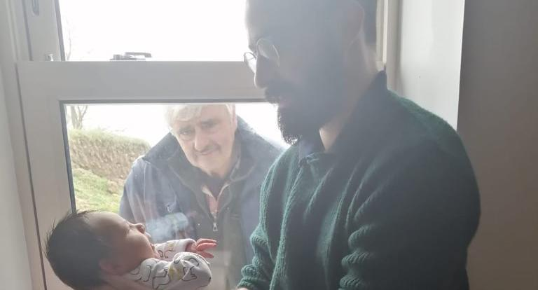 Míchéal Gallachoir's father meets his newborn son while practicing social distancing in a heartwarming, and heartbreaking new photo. Image via Twitter.