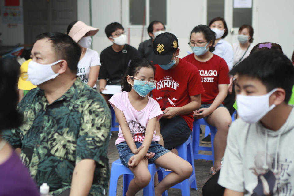 People wait in line to be tested for COVID-19 in Hanoi, Vietnam, Friday, July 31, 2020. Vietnam reported on Friday the country's first ever death of a person with the coronavirus as it struggles with a renewed outbreak after 99 days without any cases. (AP Photo/Hau Dinh)
