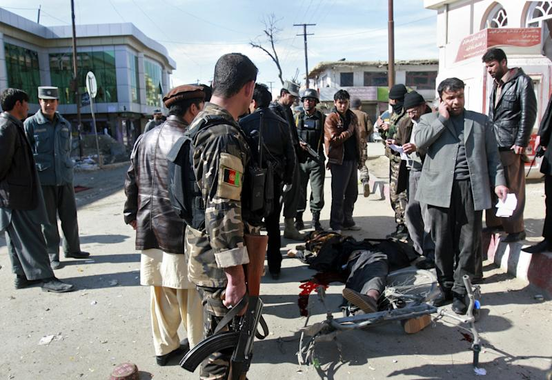 Security officers investigate the scene of a bomb in Gazni, Afghanistan, Saturday, Jan. 26, 2013. A remote controlled bomb planted on a bicycle killed several people including a police officer and a civilian in the eastern city of Ghazni and Gen. Zirawer Zahid, the provincial police chief, says another five people were wounded. (AP Photo/Rahmatullah Nikzad)