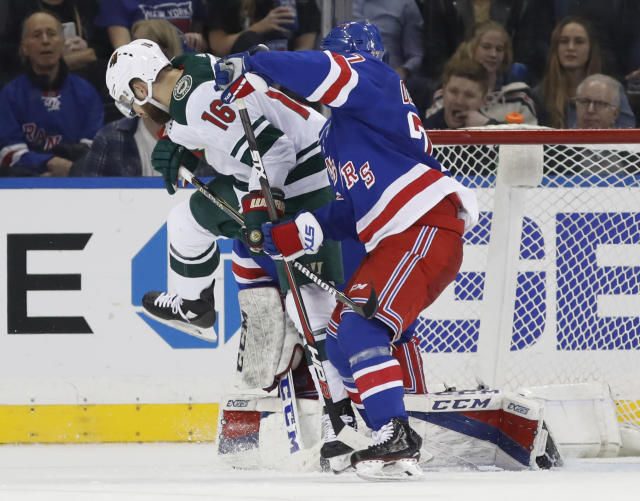 Minnesota Wild left wing Jason Zucker (16) tries to allow a puck to go through as New York Rangers defenseman Tony DeAngelo (77), right, defends against him in front of Rangers goaltender Alexandar Georgiev during the second period of an NHL hockey game in New York, Friday, Feb. 23, 2018. (AP Photo/Kathy Willens)