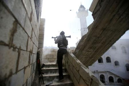 A member of the Palestinian Fatah faction fires his weapon during clashes against hard line Sunni Islamists known as the Badr group inside the Ain el-Hilweh refugee camp near Sidon