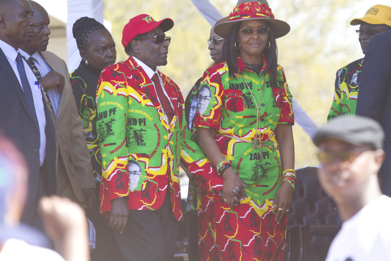 Zimbabwe's President Robert Mugabe and his wife Grace hold hands at a rally in Lupane about 170 Kilometres north of Bulawayo, Zimbabwe, Friday, July 21, 2017. Mugabe's rally is his first since his return from a routine medical review in Singapore. The world's oldest leader has launched a series of rallies targeting the youth ahead of Presidential elections set for 2018. (AP Photo/Tsvangirayi Mukwazhi)