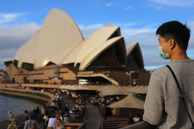 Picture of a man wearing a mask, standing outside the Sydney Opera House