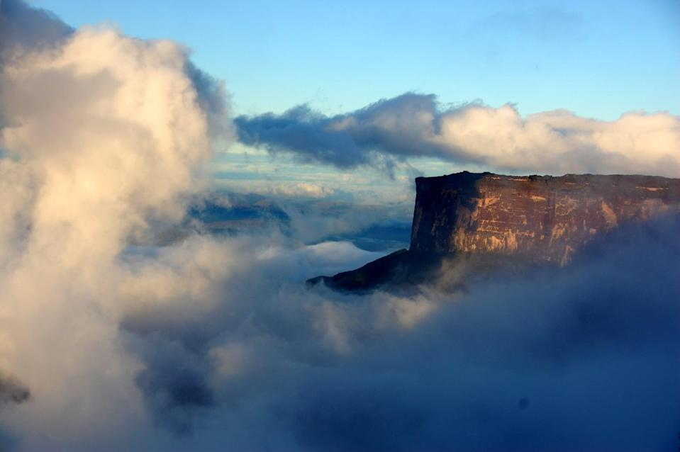 <p>Mount Roraima is a mountain range that borders Venezuela, Brazil, and Guyana. What's unique about this mountain is its flat, tabletop surface, which in the midst of clouds looks like something really magical. </p>