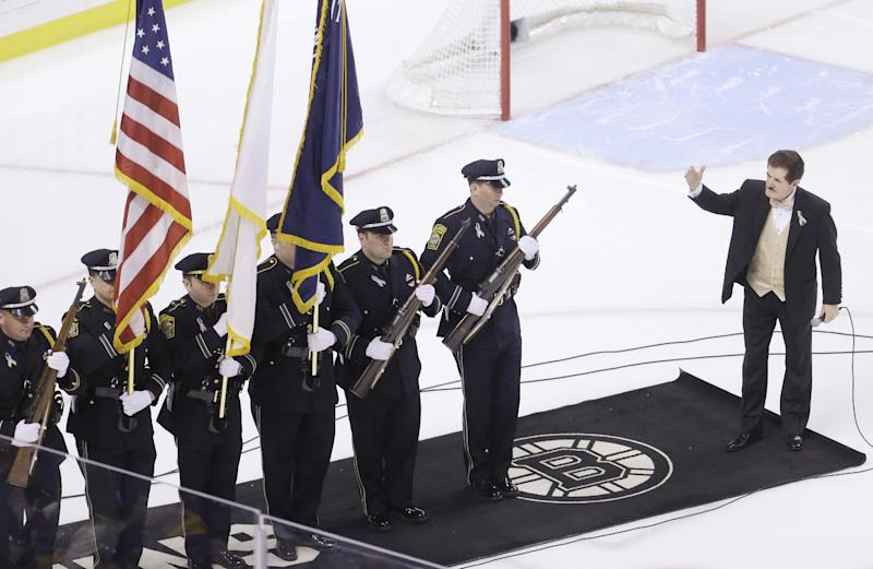 Singer Rene Rancourt, right, gestures toward a Watertown Police Honor Guard, left, on the ice before a NHL hockey game between the Boston Bruins and the Florida Panthers at the TD Garden in Boston, Sunday, April 21, 2013. The second suspect in the Monday, April 15, 2013, bombings that took place near the finish line of the Boston Marathon was captured in Watertown, Mass., Friday, April 19, 2013. (AP Photo/Steven Senne)