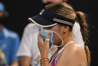 United States' Sofia Kenin holds a mask to her face during her match against Spain's Garbine Muguruza at a tuneup event ahead of the Australian Open tennis championships in Melbourne, Australia, Friday, Feb. 5, 2021.(AP Photo/Andy Brownbill)