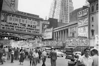 <p>View of pedestrians passing under theater marquees along West 42nd Street in Times Square.</p>