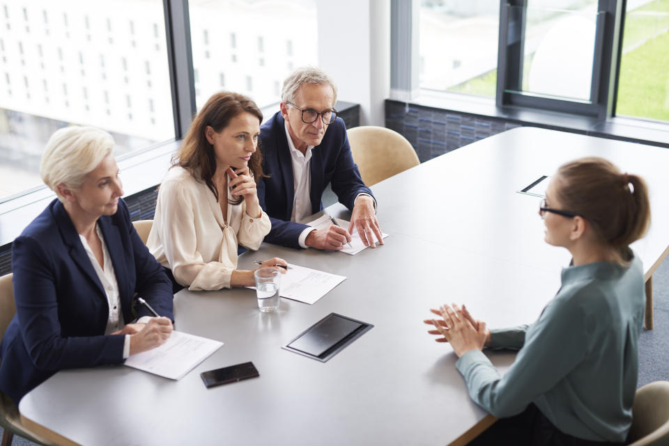 Woman during job interview and three elegant members of management
