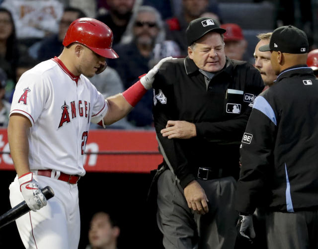 Los Angeles Angels' Mike Trout, left, comforts home plate umpire Jerry Layne, who was hit in the arm by a foul tip during the first inning of a baseball game between the Angels and the Boston Red Sox in Anaheim, Calif., Thursday, April 19, 2018. Layne left the game. (AP Photo/Chris Carlson)
