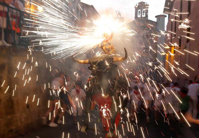 Revellers run next to the Fire Bull, a man carrying a bull figure packed with fireworks, during the San Fermin festival in Pamplona, Spain, July 7, 2019. (Photo: Jon Nazca/Reuters)