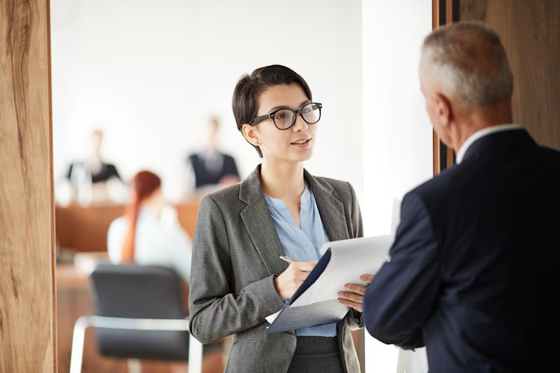 Waist up portrait of young businesswoman holding clipboard asking questions while talking to boss or business coach, copy space
