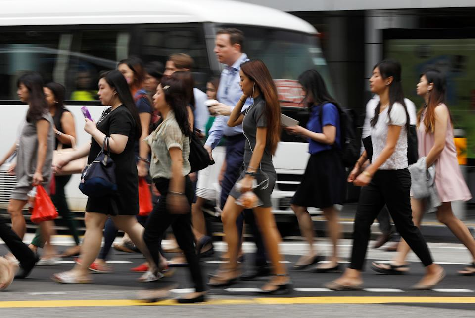 Office workers cross a street in Singapore's central business district April 27, 2017.  REUTERS/Edgar Su
