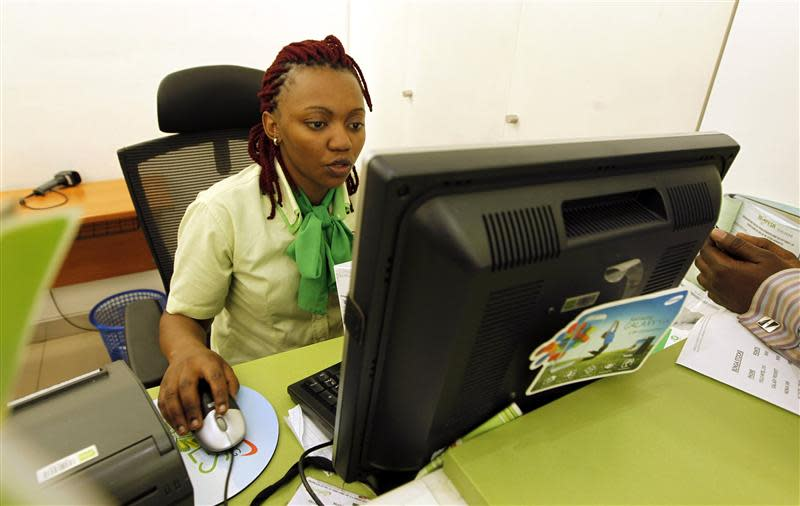An employee registers a customer for a mobile money transfer inside the Safaricom mobile phone care centre in the central business district of Kenya's capital Nairobi