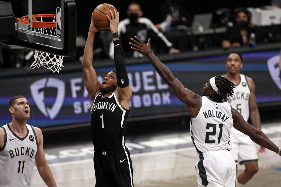 Brooklyn Nets forward Bruce Brown (1) dunks the ball past Milwaukee Bucks guard Jrue Holiday (21) during the second half of Game 1. (AP Photo/Adam Hunger)