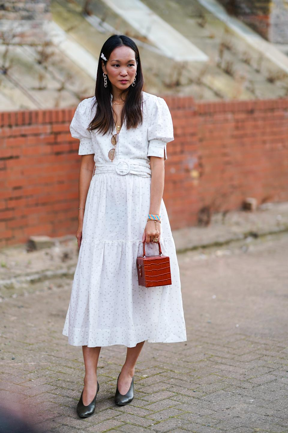 A guest is seen wearing a white dress with a small crocodile print square bag [Photo: Getty Images]