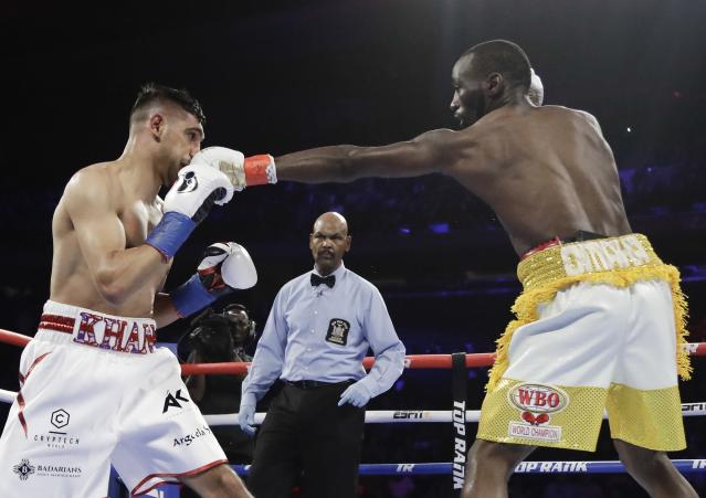 Terence Crawford, right, punches England's Amir Khan during the second round of a WBO world welterweight championship boxing match Sunday, April 21, 2019, in New York. Crawford won the fight. (AP Photo/Frank Franklin II)