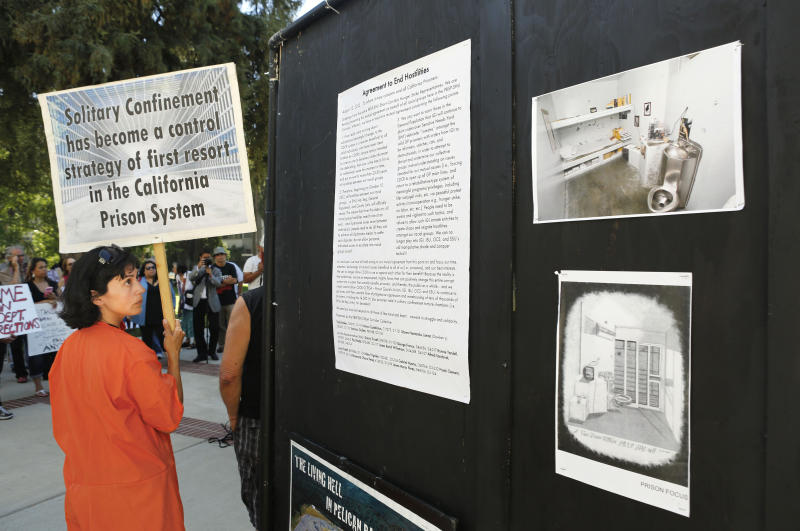 FILE -- In this Aug. 14, 2013 file photo, Diya Malika, of the Stop Mass Incarceration Network, glances at information about the Secure Housing Units in California prisons, during a rally calling for the end of solitary confinement in California prisons, at the Capitol in Sacramento, Calif. California inmates have ended their nearly two-month hunger strike protesting the prison system's isolation policies, prison officials said Thursday, Sept. 5, 2013. All inmates began accepting prison-issued meals early Thursday, Corrections Secretary Jeffery Beard said. (AP Photo/Rich Pedroncelli, file)