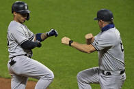 New York Yankees' Gleyber Torres (25) is congratulated by Phil Nevin (88) after hitting a two-run home run in the fifth inning of Game 1 of an American League wild-card baseball series against the Cleveland Indians, Tuesday, Sept. 29, 2020, in Cleveland. (AP Photo/David Dermer)
