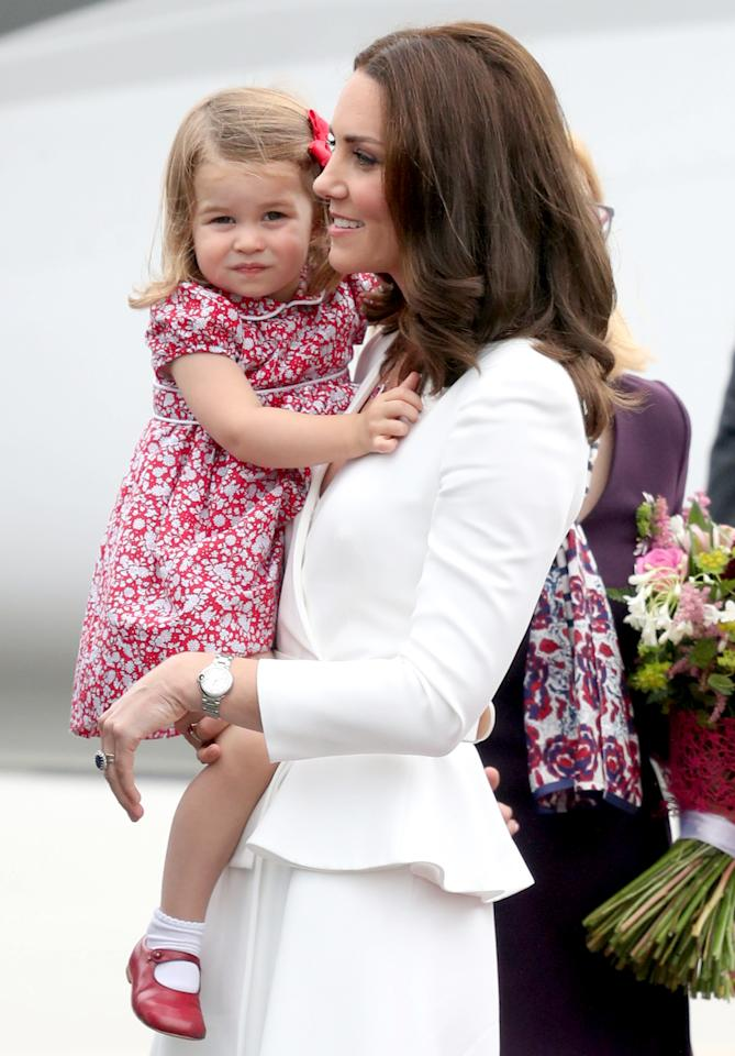 <p>Charlotte smiled for the cameras upon landing in Poland for a royal tour. The 2-year-old looked adorable in a red and white floral dress and matching Mary Janes while resting in mom's arms.</p>