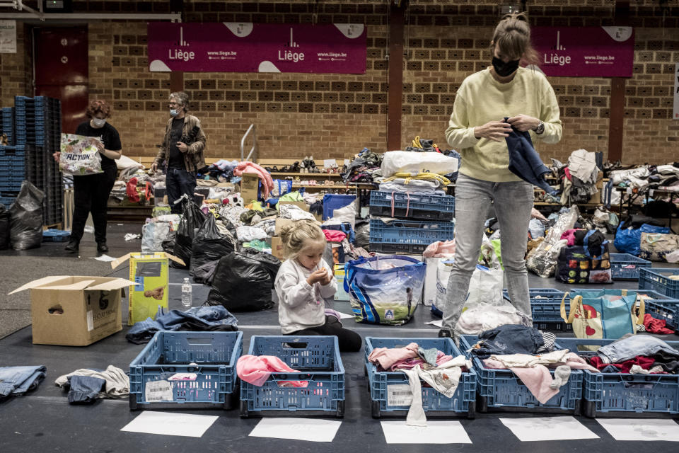 A woman sorts through clothing in a shelter for residents after flooding in Angleur, Province of Liege, Belgium, Friday July 16, 2021. Severe flooding in Germany and Belgium has turned streams and streets into raging torrents that have swept away cars and caused houses to collapse. (AP Photo/Valentin Bianchi)