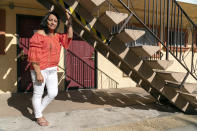 In this Wednesday, June 30, 2021, photo Veronica Perez poses outside at her new home at the Mollie Mason Project Homekey site in Los Angeles. Perez took residence in one of 6,000 new units built statewide over the last year as part of Project Homekey. The California program started in June 2020 is re-purposing vacant hotels, motels and other unused properties as permanent supportive housing for the homeless. (AP Photo/Damian Dovarganes)