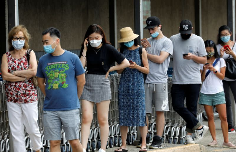 People wear protective face masks outside at a shopping plaza in Edgewater, New Jersey