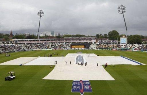 Groundstaff cover the pitch as rain delays the start