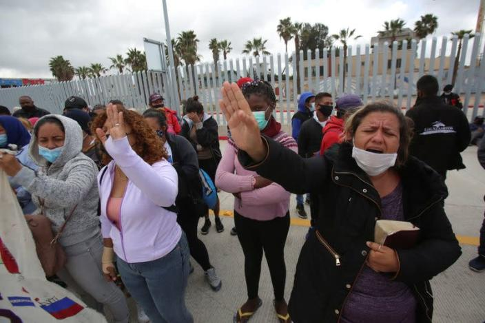 Asylum-seeking migrants from Mexico and Central America pray near the San Ysidro Port of Entry with the U.S., in Tijuana