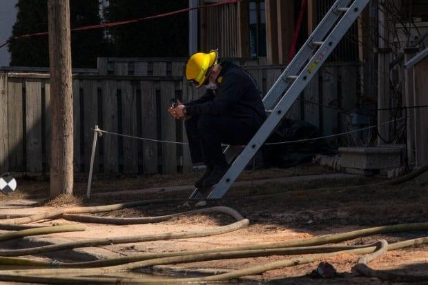 A firefighters reacts as he sits outside the ruins of a house in Oshawa, Ont. The bodies of four people, two children and two male adults, have been recovered from the house.