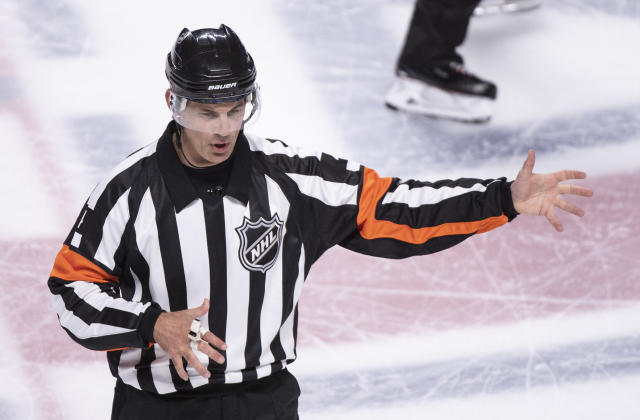 In this photo taken Sept. 17, 2018, referee Wes McCauley, top, calls a penalty as the Montreal Canadiens face the New Jersey Devils during preseason NHL hockey game action in Montreal. An informal poll of NHL players leaves no doubt as to who the most popular referee is: Veteran McCauley. (Paul Chiasson/The Canadian Press via AP)