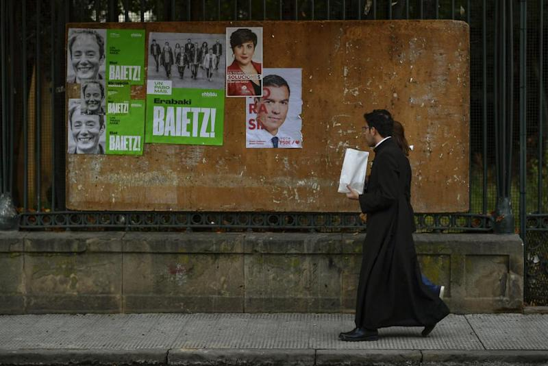 A priest in Navarre walks past electoral campaign posters, one featuring the prime minister, Pedro Sánchez