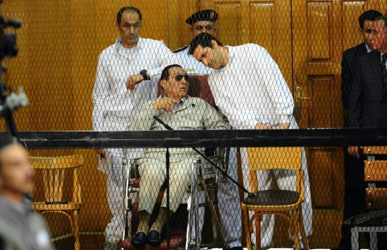Former Egyptian president Hosni Mubarak, who faced multiple charges after his overthrow, including over the deaths of protesters in 2011 and for corruption, appeared with his two sons Alaa (R) and Gamal at their trial in Cairo in September 2013 (AFP Photo/AHMED EL-MALKY)