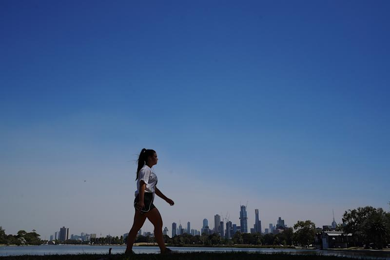 A walker braves the heat to walk around Albert Park lake during hot weather in Melbourne.
