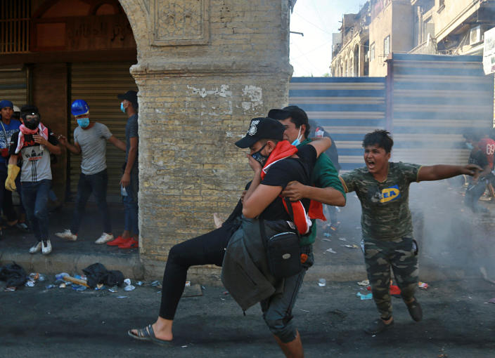 An injured protester is rushed to a hospital during clashes between Iraqi security forces and anti-government protesters in the al-Rasheed street in Baghdad, Iraq, Friday, Nov. 8, 2019. The demonstrators complain of widespread corruption, lack of job opportunities and poor basic services, including regular power cuts despite Iraq's vast oil reserves. They have snubbed limited economic reforms proposed by the government, calling for it to resign. (AP Photo/Khalid Mohammed)