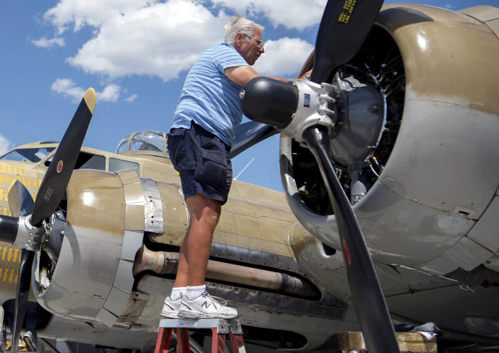 "In This July 1, 2019 photo, Ernest ""Mac"" McCauley, a veteran pilot who volunteers with the Collings Foundation, works on one of the nine-cylinder radial engines on a B-17 Flying Fortress bomber on display at the Spokane International Airport in Spokane, Wash. McCauley, 75, of Long Beach, Calif., and his co-pilot were among seven people killed when the bomber crashed and burned Wednesday, Oct. 2, at Bradley International Airport in Windsor Locks, Conn. (Jesse Tinsley/The Spokesman-Review via AP)"