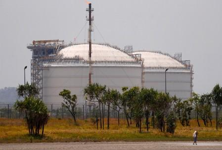 FILE PHOTO: A woman carrying a bag containing firewood walks in front of two Liquefied Natural Gas (LNG) storage tanks at the ExxonMobil PNG Limited-operated LNG plant at Caution Bay, located on the outskirts of Port Moresby