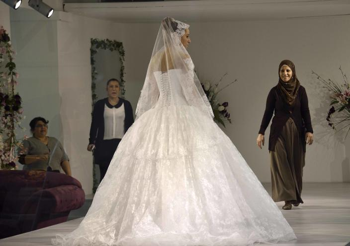 """In this picture taken March 7, 2013 a Turkish woman wears a wedding dress in one of a dozen Turkish wedding stores in Duisburg-Marxloh, western Germany. Germany's experience with """"guest workers"""" offers lessons for the United States as it debates immigration reform, including whether to provide a path to citizenship for unskilled foreign laborers. (AP Photo/Martin Meissner)"""