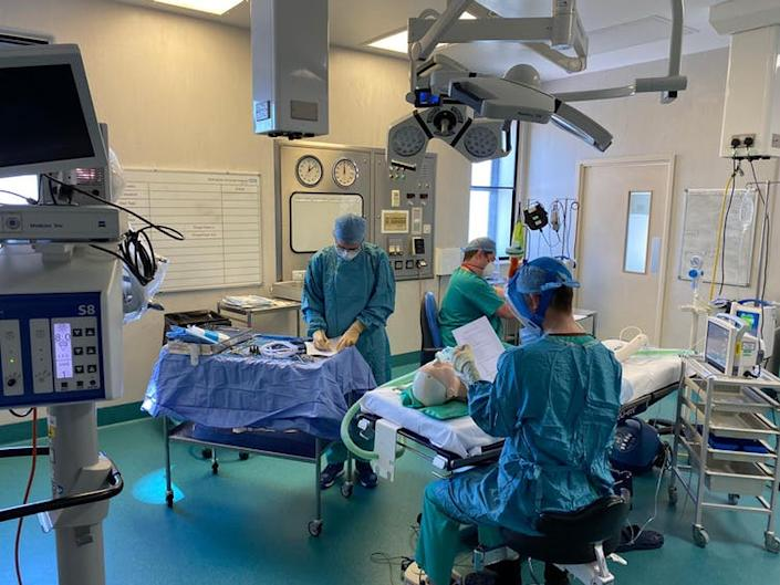 Three people wearing surgical scrubs in an operating theatre.