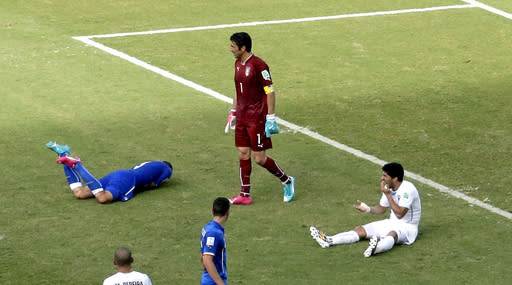 Italy's Giorgio Chiellini, left, lays on the pitch after Uruguay's Luis Suarez, right, ran into him with his teeth during the group D World Cup soccer match between Italy and Uruguay at the Arena das Dunas in Natal, Brazil, Tuesday, June 24, 2014. (AP Photo/Hassan Ammar)