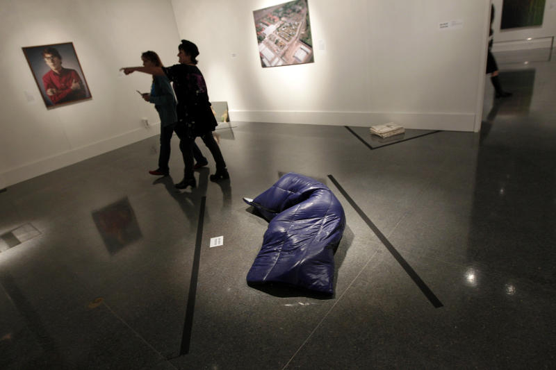 """In this Wednesday, Nov. 14, 2012 photo, museum patrons walk past a painted bronze sleeping bag, titled """"Nomad,"""" by artist Gavin Turk, at the New Orleans Museum of Art in New Orleans. The piece is part of """"Lifelike,"""" a traveling exhibit at the New Orleans Museum of Art through Jan. 27. (AP Photo/Gerald Herbert)"""
