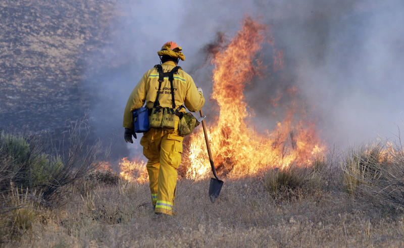 A Los Angeles County firefighter approaches a fire along a road in Lake Hughes, Calif., early Sunday, June 2, 2013. Erratic winds fanned a blaze in the Angeles National Forest to nearly 41 square miles early Sunday, after fast-moving flames triggered the evacuation of nearly 1,000 homes in Lake Hughes and Lake Elizabeth, officials said. (AP Photo/Reed Saxon)