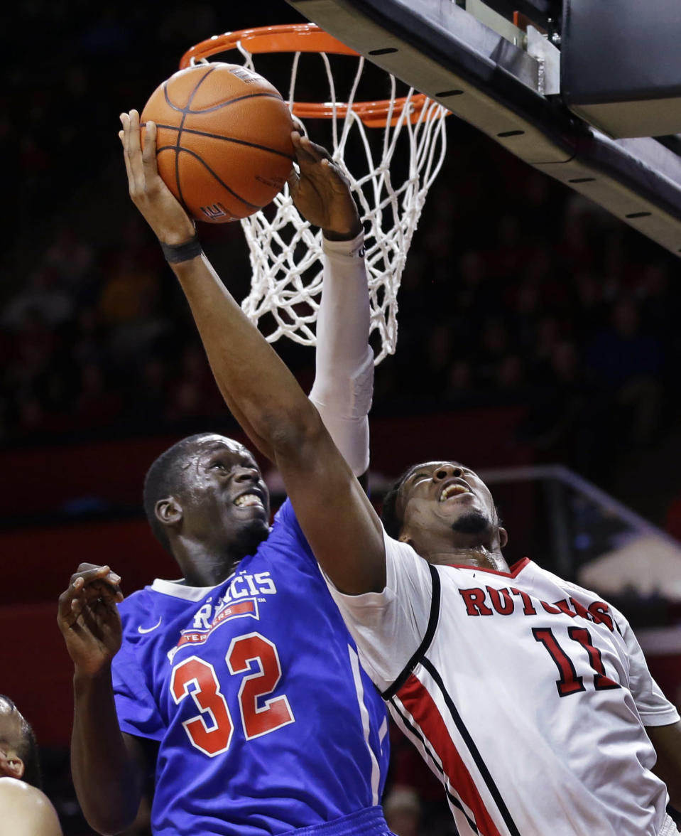 Rutgers' Kadeem Jack (11) takes a shot as St. Francis Brooklyn's Amdy Fall (32) tries to make a block during the first half of an NCAA college basketball game Sunday, Nov. 23, 2014, in Piscataway, N.J. (AP Photo/Mel Evans)
