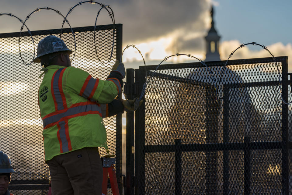 FILE - In this Jan. 18, 2021, file photo, workers install razor wire atop fencing around the U.S. Capitol perimeter at sunset, in Washington. (AP Photo/J. Scott Applewhite, File)