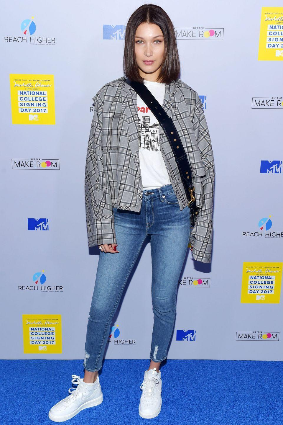 <p>In a grey plaid jacket, white graphic tee, crossbody bag, cropped jeans and white sneakers at a National College Signing Day event in NYC.</p>