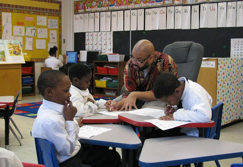 FILE - In this March 15, 2011 file photo, teacher Calvin Hobbs works with students at African-centered Timbuktu Academy of Science and Technology in Detroit. A proposal that Gov. Rick Snyder commissioned for overhauling public education in Michigan and change how the state pays for student learning was released Monday, Nov. 19, 2012. The Oxford Foundation-Michigan placed a draft of the Michigan Public Education Finance Act on its website. If legislators approve it, the proposal would replace the School Aid Act of 1979. (AP Photo/Corey Williams, File)
