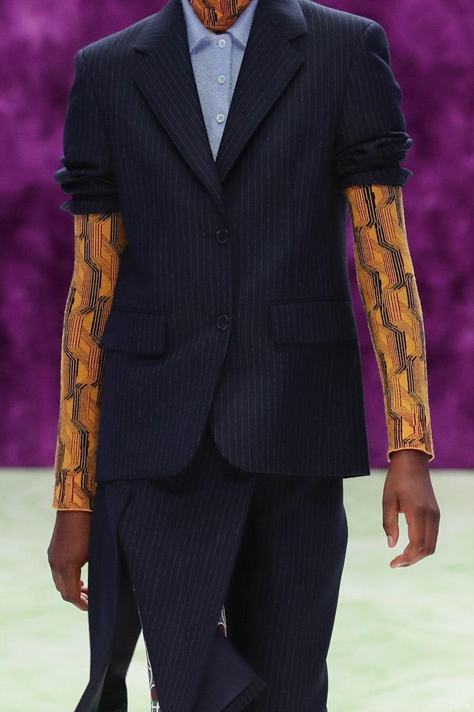<p>Rolling up your blazer creates a mix-match pattern reveal and gives your whole look an air of '80s nonchalant cool. </p><p><strong>Insider tip:</strong> Use a comfortably fitting rubber band over the suit sleeve and then push it up to the desired place. The rubber band will help keep the sleeve up—just make sure to hide it in the folds.</p><p><em>Pictured: Prada</em></p>